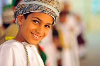 Oman, Muscat, close-up portrait of a cheerful boy in a turban smiling